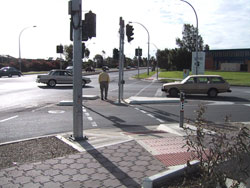 Figure 10-6. Signalized left turn lane with APS mounted close to the crosswalk locations. Three APS are on the splitter island, one for each crossing.