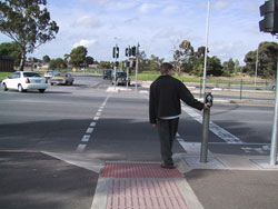 Figure 10-8. Typical APS location in relation to the crosswalk and sidewalk. Australian curb ramp standards allow a steeper slope than allowed by US standards.