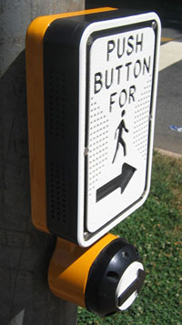 Figure 4-2. This APS has a high-contrast, raised tactile arrow on the pushbutton and a high-contrast, recessed tactile arrow on the sign above the button