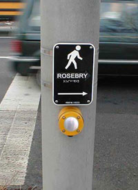 Figure 4-8. A Braille street name is pictured on a sign above the pushbutton. The street name is also provided in high contrast large print (but not raised print) at this location