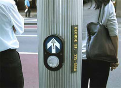 Figure 4-9. Example from Australia; a sign with raised print and Braille is mounted vertically on a round pole to the right of an APS. The sign reads