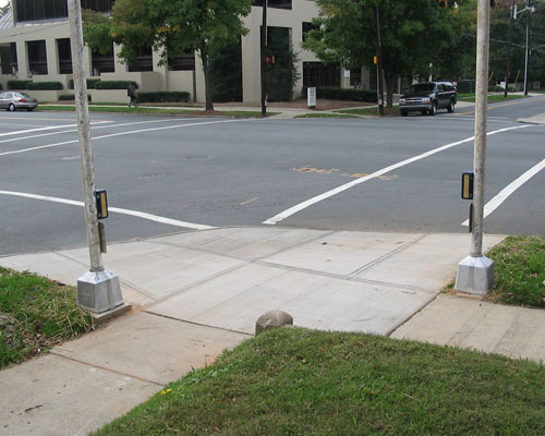 Figure 6-13. APS installed in this reconstruction location are in accordance with MUTCD and Proposed PROWAG in that they are beside a level landing and separated from each other by at least 10 feet (3 m). Both APS are located on the intersection side of their poles.