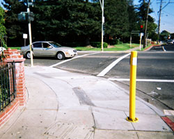 Figure 6-16. APS are positioned appropriately at this intersection by the addition of a stub pole for one crosswalk. The stub pole holding the APS for the crosswalk at right is simply bolted to the sidewalk. The other APS is mounted on the pole that supports the pedhead.