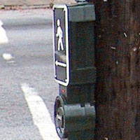 Figure 6-23. Mounted on a wooden pole, an additional mounting bracket is installed to allow the wires to run from the conduit into the top of the pushbutton-integrated device.