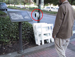 Figure 7-4. Not only is the pushbutton in the bushes and out of reach range from the sidewalk, construction barriers have been stored against the pole, preventing all pedestrians from reaching the pushbuttons.