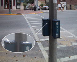 Figure 9-10. Mounting of two Prisma pushbutton units on a single pole. See arrows on insert detail for the orientation of the tactile arrow on the top of each unit. Both devices make the same sound during the WALK indication, which is acceptable in this installation since there is exclusive pedestrian phasing.