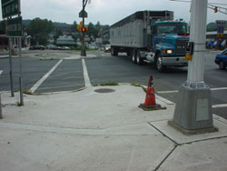 Figure 9-8. Installation of two pushbuttons on a single pole (only a single push-button is visible in the photo). While the push-button is in line with the crosswalk, the pedestrian must travel over 10 feet before reaching the street and the beginning of the crosswalk.