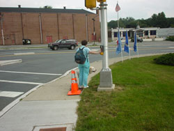 Figure 9-9. APS mounted on signal pole for crossing signalized right turn lane. Pedestrian who is blind is waiting with her hand on the pushbutton for the vibrotactile WALK indication. After the WALK indication begins, she must turn, and cross the sidewalk before beginning to cross the street.